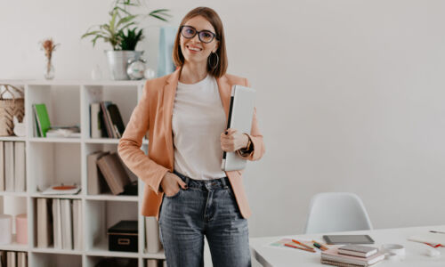 Satisfied female entrepreneur posing with laptop in hand against background of her minimalistic office